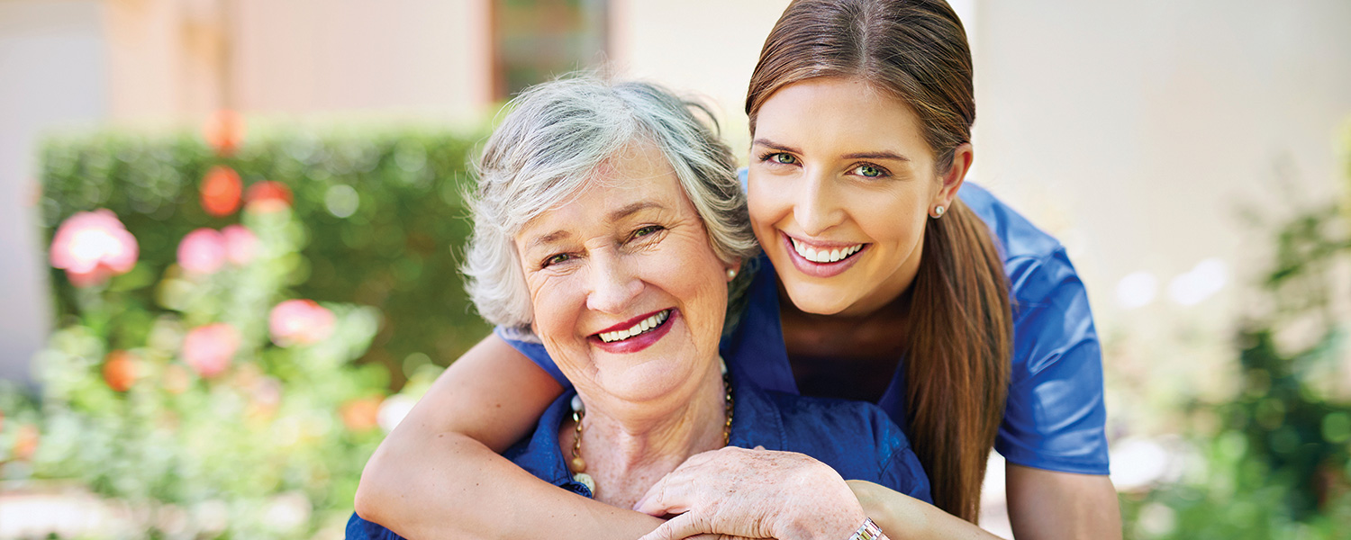 Smiling caregiver with her arms around smiling senior woman.