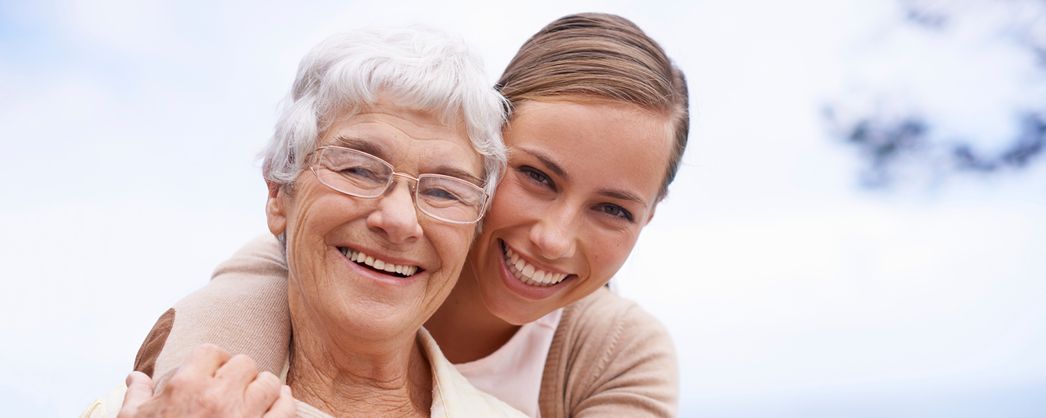 Smiling senior woman being embraced by smiling younger woman.