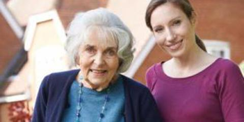 Senior woman in a blue sweater next to a younger woman in a mulberry sweater.
