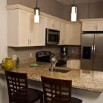 Full kitchen in independent senior living apartment with breakfast nook, granite countertop and stainless steel appliances.