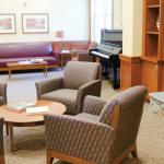 Common space in the memory care community of Bridges® by EPOCH at Westford, featuring a piano and comfortable seating.